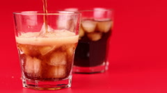cola pour into glass on a red background - stock footage