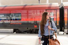 Female backpacker arriving in train station, Salzburg, Austria Stock Photos