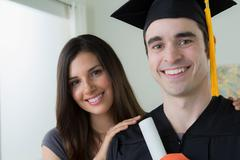 Man wearing mortarboard and graduation gown with woman Stock Photos