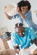 Mid adult woman pouring polystyrene over man's head Stock Photos