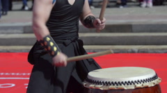 Japanese artist playing on traditional taiko drums - stock footage