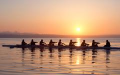Nine people rowing at sunset Stock Photos