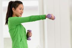 Woman lifting dumbbell with one arm forward - stock photo