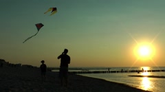 Family having fun with a kite on the beach in the evening Stock Footage