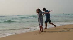 Beautifel happy pair palying and having fun at the beach. Pregnant woman hugging - stock footage
