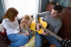 Husband & wife entertaining child Stock Photos