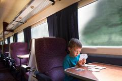 Young boy playing patience on train - stock photo