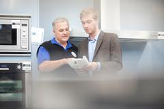 Young man looking at appliance brochure in showroom - stock photo