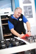 Kitchen appliance salesman in showroom - stock photo