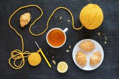Lemon tea, yellow crocheting and croissants Stock Photos