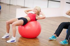 Young woman lying on exercise ball in aerobics class Stock Photos