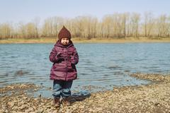 Little girl standing on a riverbank - stock photo