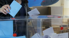 Woman vote on elections, putting blue and white ballot in boxes, polls close up. Stock Footage
