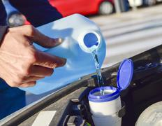 Filling the tank of windshield washer fluid Stock Photos