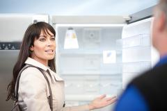 Woman looking at fridge in showroom Stock Photos