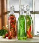 Three bottles of pickled herbs on windowsill Stock Photos