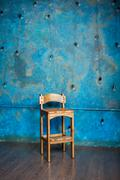 Old wooden chair in grunge room with blue wall - stock photo