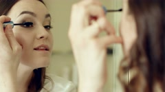 Model applying mascara to the eyelashes looking in a mirror - stock footage