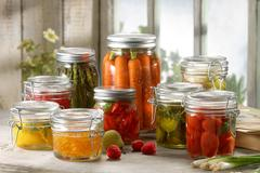 Variety of fruit and vegetables pickled in jars - stock photo