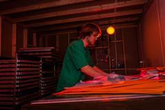 Man working in darkroom in screen printing workshop Stock Photos