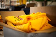 Open cardboard box containing screen printed t-shirts - stock photo