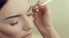 Makeup artist applies shadows on the model's eyes Stock Footage