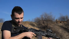 Man firing customised russian machine gun, medium Stock Footage
