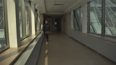 Llittle girl walking in the hallway of a skyscraper Stock Footage