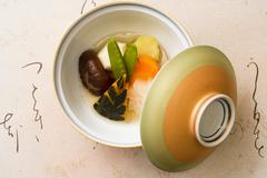 Still life of bowl and lid with fresh steamed vegetables - stock photo