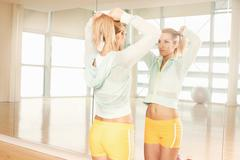 Women doing her hair in mirror in gymnasium Stock Photos