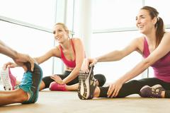 Friends stretching in gymnasium Stock Photos