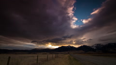 Absaroka mountains at sunrise over dirt road in Montana Stock Footage