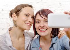 Portrait of two beautiful girls making selfies at home Kuvituskuvat