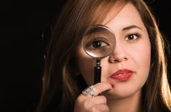 Young woman facing camera holding magnifying glass over right eye creating Stock Photos