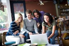 Group of people gathered around computer in cafe - stock photo