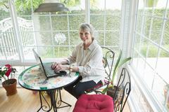 Senior woman using latpop in conservatory, portrait Stock Photos