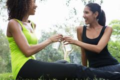 Mid adult and young woman tasting with water bottles in park Stock Photos