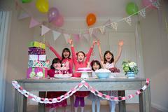 Girls cheering at birthday party Stock Photos