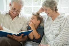 Grandparents showing boy photo album on sofa Kuvituskuvat