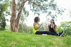 Mid adult and young woman relaxing in park Stock Photos