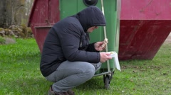 Homeless with food near waste container - stock footage