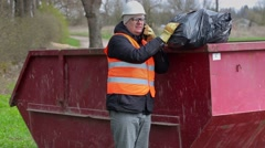 Worker talking on smart phone and keeps garbage bag on waste container - stock footage