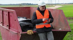 Worker using tablet PC and talking near waste container Stock Footage