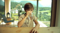 Cute boy drinking glass of water in house in the mountains dolly shot - stock footage