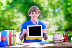 Child with tablet computer on school yard - stock photo