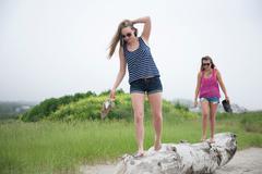 Young women walking along log on beach Stock Photos