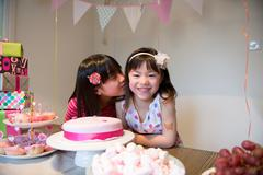 Girl kissing friend at birthday party Stock Photos