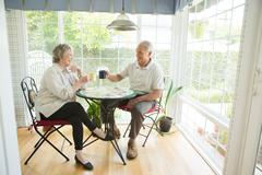 Senior couple at table in conservatory Stock Photos