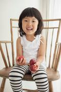 Girl sitting on wooden chair holding apples, portrait - stock photo