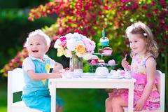 Kids having fun at garden tea party - stock photo